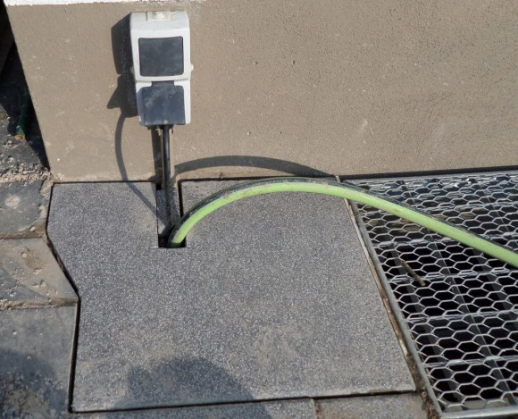 Unter dieser Steinplatte verbrigt sichd as DIN 110 Rohr in dem der Schlauch und das Kabel verlegt worden sind